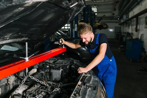 Mecânico de automóveis elevando o motor do carro