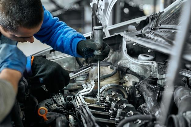 Mecânico de automóveis em uniforme azul, substituindo velas de incandescência no motor