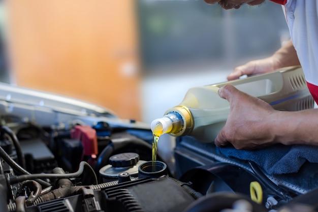Mecânico de automóveis enche um óleo lubrificante novo