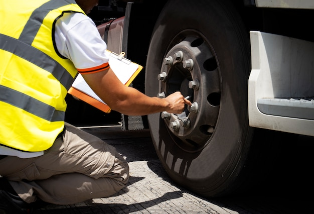 Mecânico de automóveis está inspecionando a roda do caminhão.