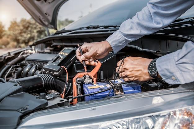 Mecânico de automóveis está usando uma ferramenta de equipamento de medição para verificar a bateria do carro