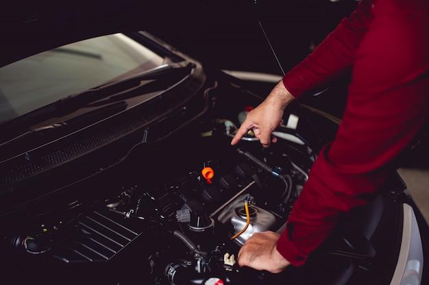 Mecânico de automóveis está verificando a disponibilidade de um companheiro de condução bom e seguro.