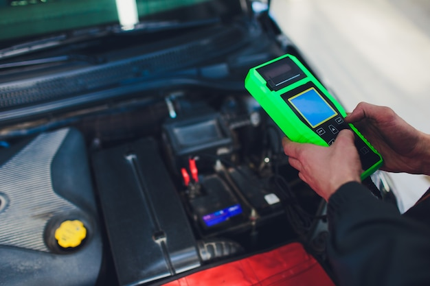 Mecânico de automóveis está verificando o motor e segurando o medidor de bateria.