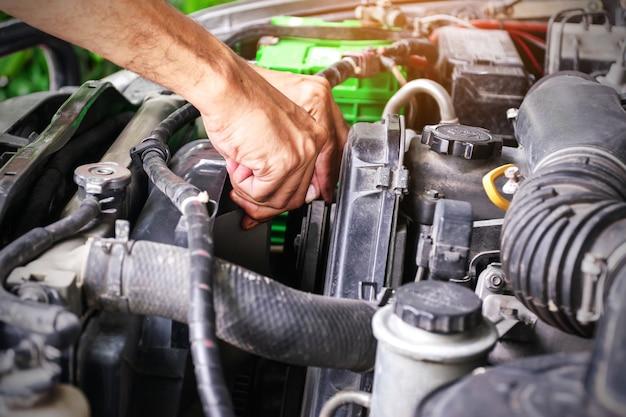 Mecânico de automóveis está verificando os ventiladores de um carro, a indústria automotiva e o conceito de garagem.