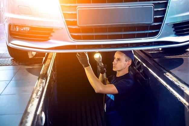 Mecânico de automóveis examinando a suspensão do automóvel levantado na estação de serviço de reparo.