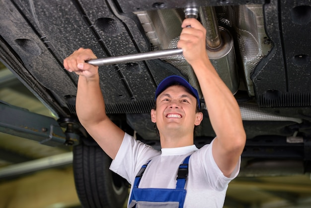 Mecânico de automóveis, examinando a suspensão do carro.