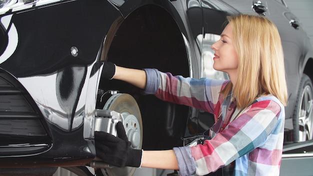 Mecânico de automóveis feminino trabalha em sua própria oficina de reparação automóvel. um trabalho favorito, um modo de vida