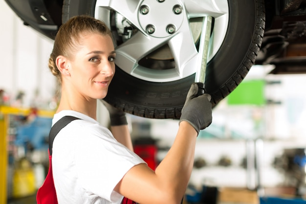 Mecânico de automóveis feminino trabalhando no automóvel levantado