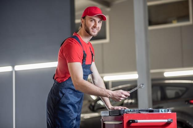 Mecânico de automóveis, ferramentas. jovem mecânico de automóveis barbudo de macacão azul com uma chave inglesa em pé perto da caixa de ferramentas de bom humor