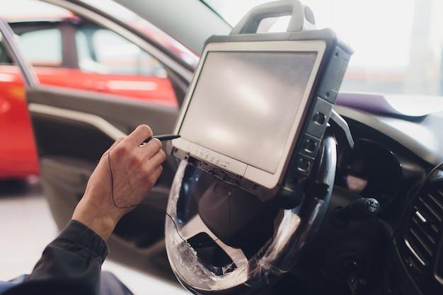 Mecânico de automóveis mantém um veículo com a ajuda de um computador de diagnóstico - tecnologia moderna na oficina de automóveis.