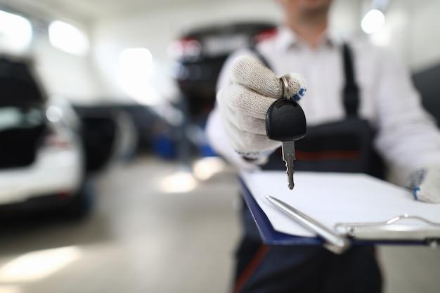 Mecânico de automóveis na oficina, estendendo as chaves