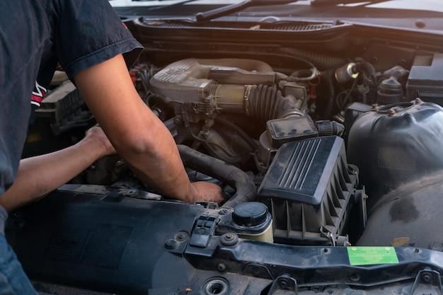 Mecânico de automóveis olhando e análise para reparar o motor na garagem