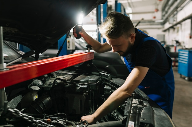Mecânico de automóveis, olhando para a sala de máquinas do carro