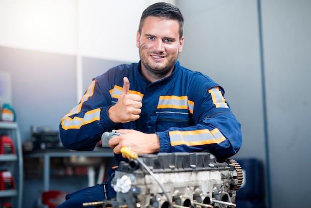 Mecânico de automóveis parado junto ao motor do carro com os polegares para cima.