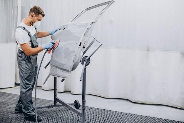 Mecânico de automóveis polindo carro antes de pintar