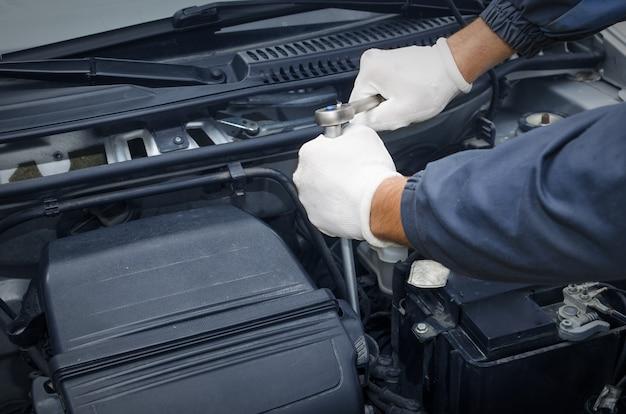 Mecânico de automóveis profissional em oficina consertando carros