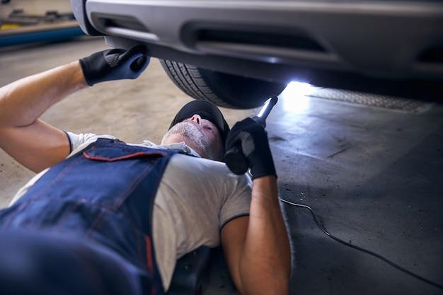 Mecânico de automóveis profissional inspecionando carro em estação de serviço