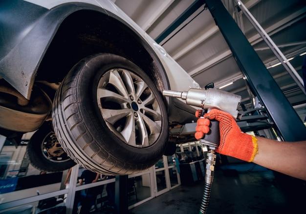 Mecânico de automóveis profissional trabalhando com chave pneumática no serviço de reparo de automóveis.