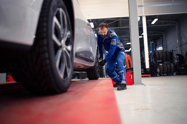 Mecânico de automóveis profissional trabalhando em oficina de veículos, reparos e manutenção de automóveis.