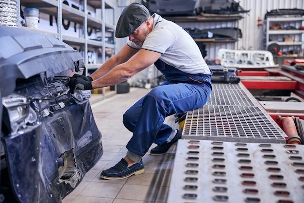 Mecânico de automóveis profissional trabalhando em oficina mecânica