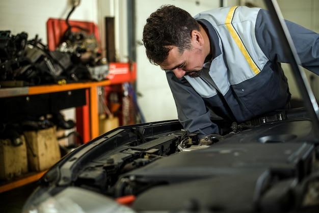 Mecânico de automóveis profissional trabalhando no serviço de reparação automóvel.