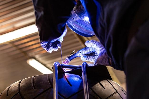 Mecânico de automóveis profissional trabalhando no serviço de reparo de auto na máquina de corte de gás argônio