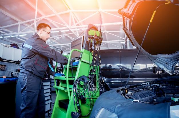 Mecânico de automóveis profissional trabalhando no serviço de reparo de automóvel.