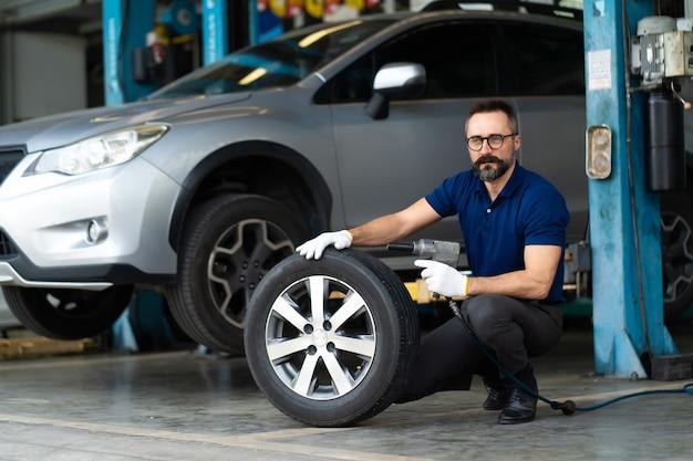 Mecânico de automóveis profissional trocando a roda do carro na oficina de manutenção e serviço automotivo