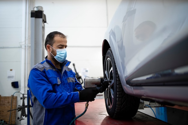 Mecânico de automóveis profissional usando máscara facial devido ao vírus corona segurando uma pistola de parafuso pneumática e trocando as rodas do veículo.