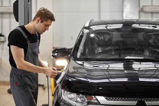 Mecânico de automóveis que trabalha duro polindo carro em oficina mecânica