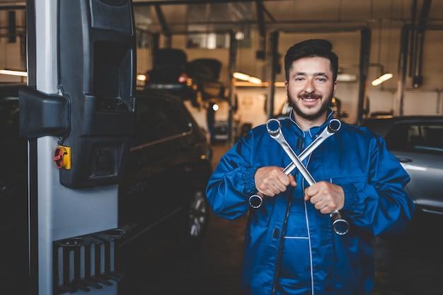 Mecânico de automóveis, reparando carros na garagem de serviço
