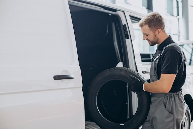 Mecânico de automóveis segurando pneus novos perto da van branca