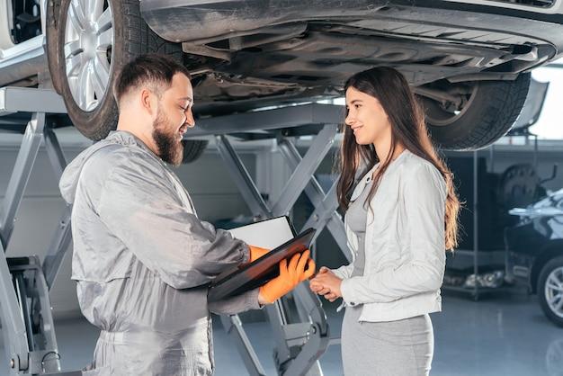 Mecânico de automóveis segurando uma prancheta conversando com uma cliente na oficina de qualidade do centro de reparos de automóveis