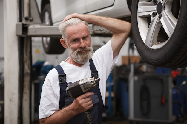 Mecânico de automóveis sênior confiante sorrindo para a câmera, trabalhando com uma chave de torque elétrica em sua oficina