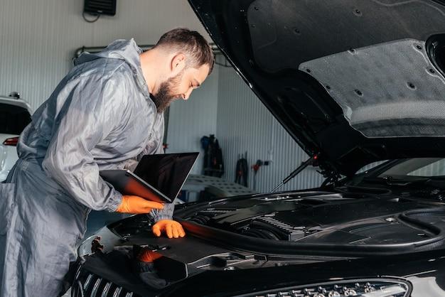 Mecânico de automóveis trabalhando com um laptop no serviço de conserto de automóveis, verificando o motor do carro