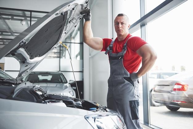 Mecânico de automóveis trabalhando em garagem. serviço de reparo.