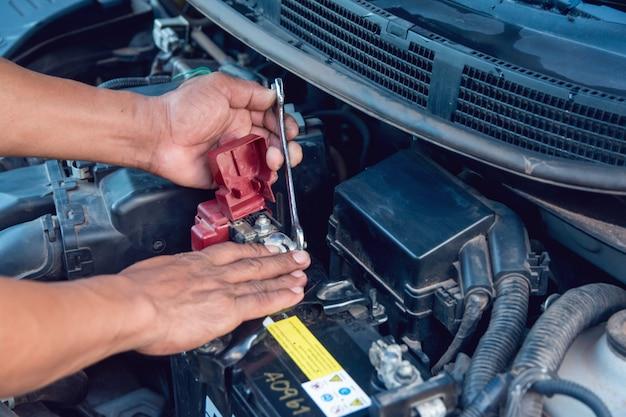 Mecânico de automóveis trabalhando instale a bateria com chave na garagem. serviço de reparo.