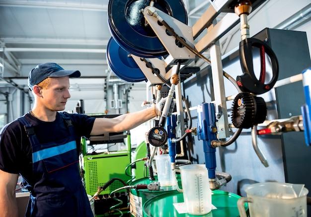 Mecânico de automóveis troca óleo do motor