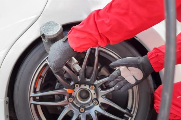 Mecânico de automóveis trocando a roda de carro de corrida