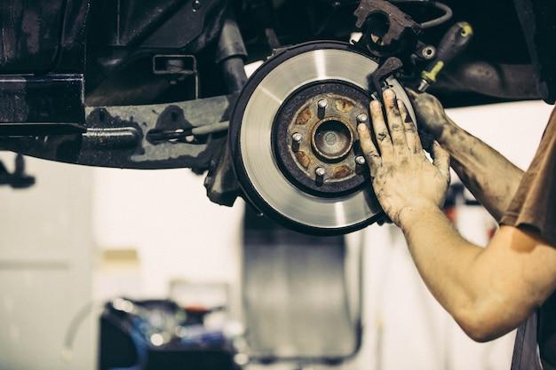 Mecânico de automóveis trocando os freios do carro, conceito de transporte