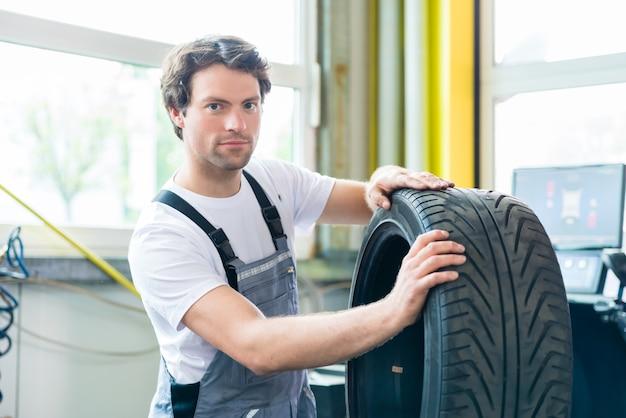 Mecânico de automóveis trocando pneu em oficina automotiva