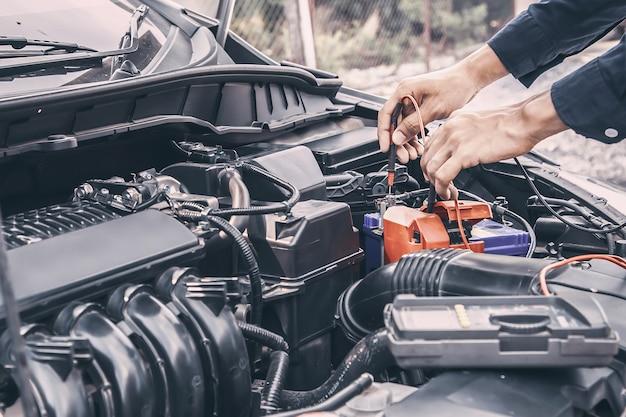 Mecânico de automóveis, usando a ferramenta de equipamento de medição para corrigir a verificação da bateria do carro