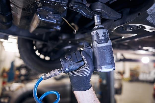 Mecânico de automóveis usando chave de impacto na oficina mecânica