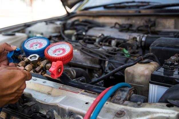 Mecânico de automóveis usando ferramenta de equipamento de medição para enchimento de ar condicionado de automóveis.
