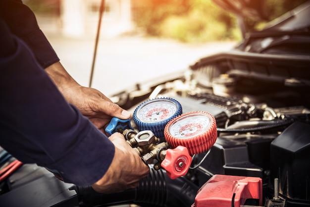 Mecânico de automóveis usando ferramenta de medição para encher condicionadores de ar de automóveis.