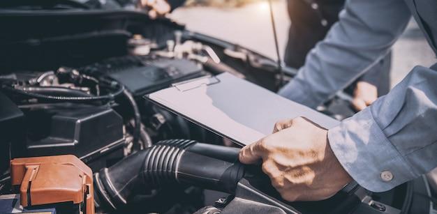 Mecânico de automóveis usando lista de verificação para sistemas de motor de carro após consertado