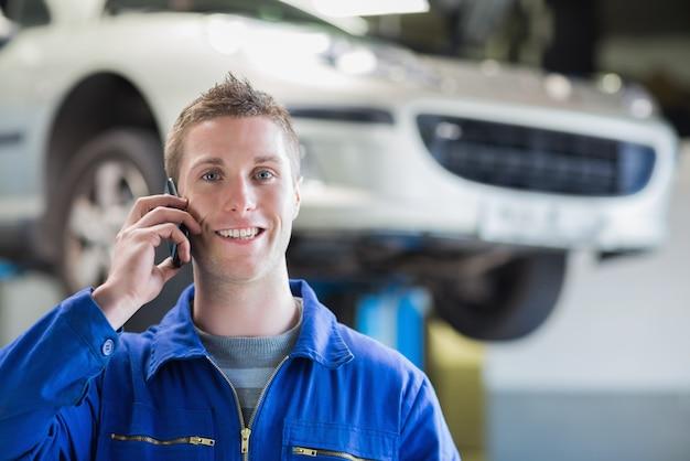 Mecânico de automóveis, usando telefone celular