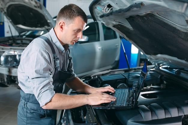 Mecânico de automóveis usando um laptop para diagnosticar e verificar as peças do motor do carro para conserto e reparo