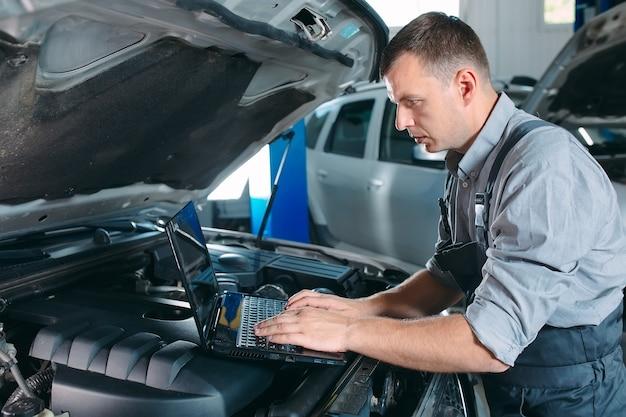 Mecânico de automóveis usando um laptop para diagnosticar e verificar o motor do carro