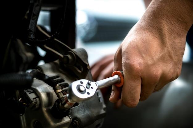 Mecânico de automóveis, usando uma chave de reparo do dínamo auto.